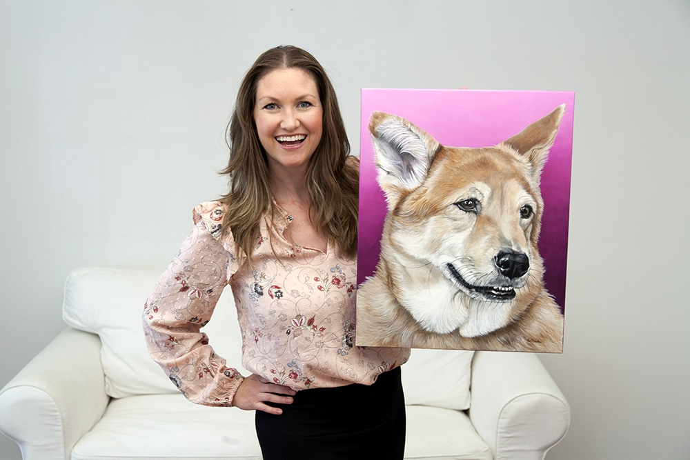 Erica Eriksdotter holding her custom dog portrait of a german sheperd and chow mix dog