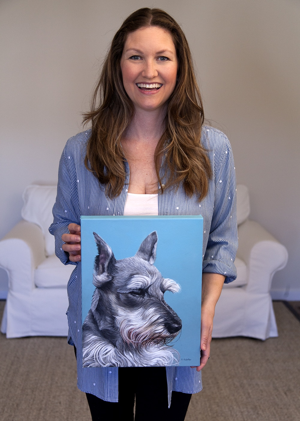 Photo of fine arts painter Erica Eriksdotter holding her custom dog portrait of a schnauzer