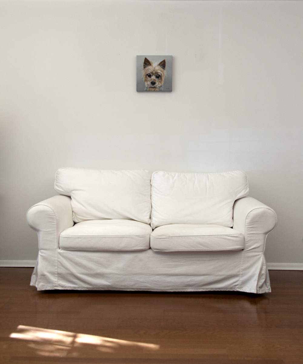 A custom dog portrait of a yorkshire terrier by fine arts painter Erica Eriksdotter hangs above a white loveseat