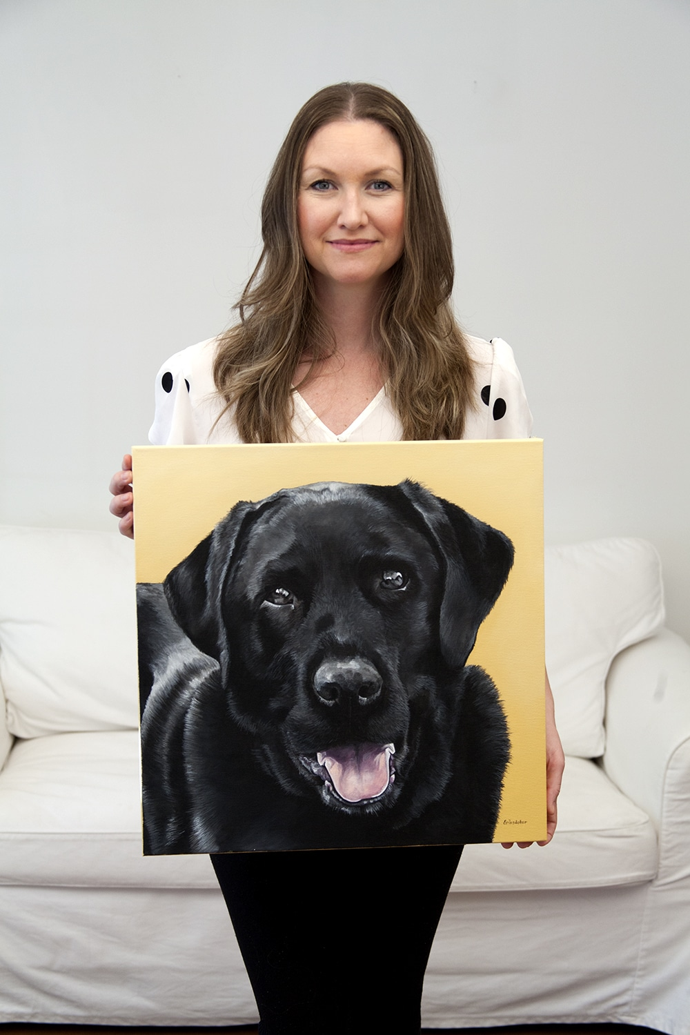 Erica Eriksdotter holding her custom dog portrait of a black labrador
