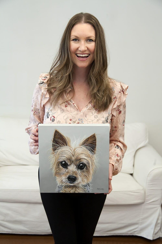 Erica Eriksdotter holds her custom dog portrait of a yorkshire terrier dog