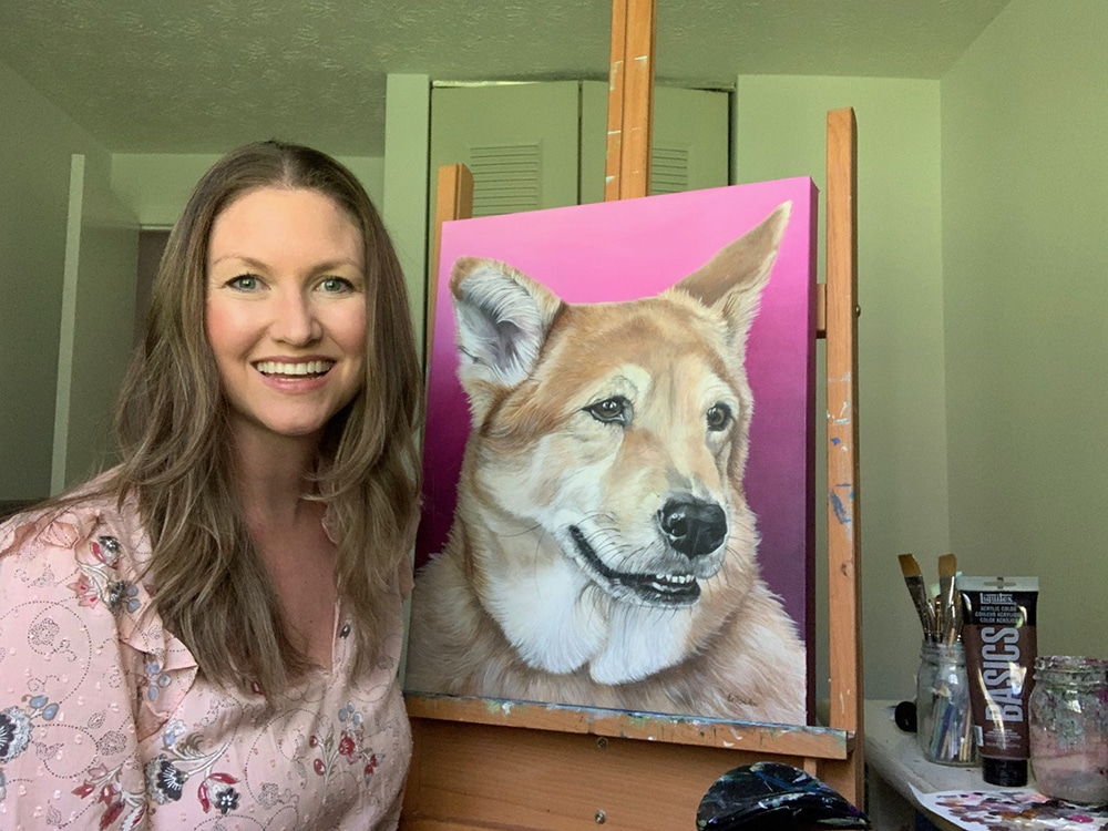 Fine arts painter Erica Eriksdotter sits by her easel with a custom painting of a black lab