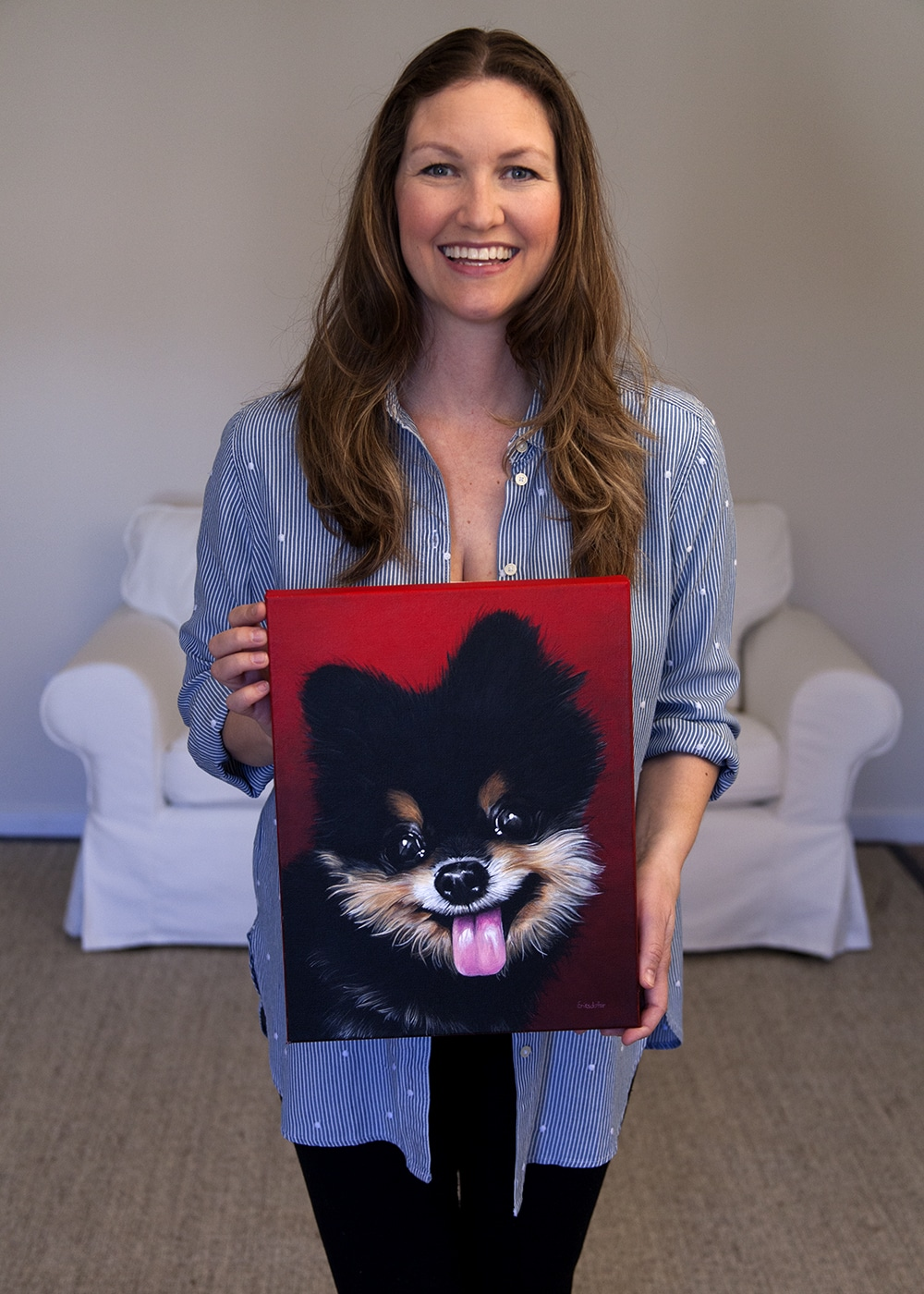 Photo of fine arts painter Erica Eriksdotter holding her custom dog portrait of a pomeranian dog by fine arts painter Erica Eriksdotter