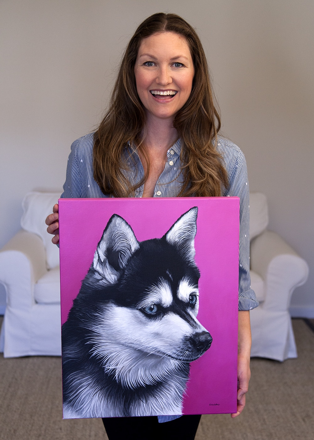 Photo of fine arts painter Erica Eriksdotter holding her custom dog portrait of an Alaskan Klee Kai