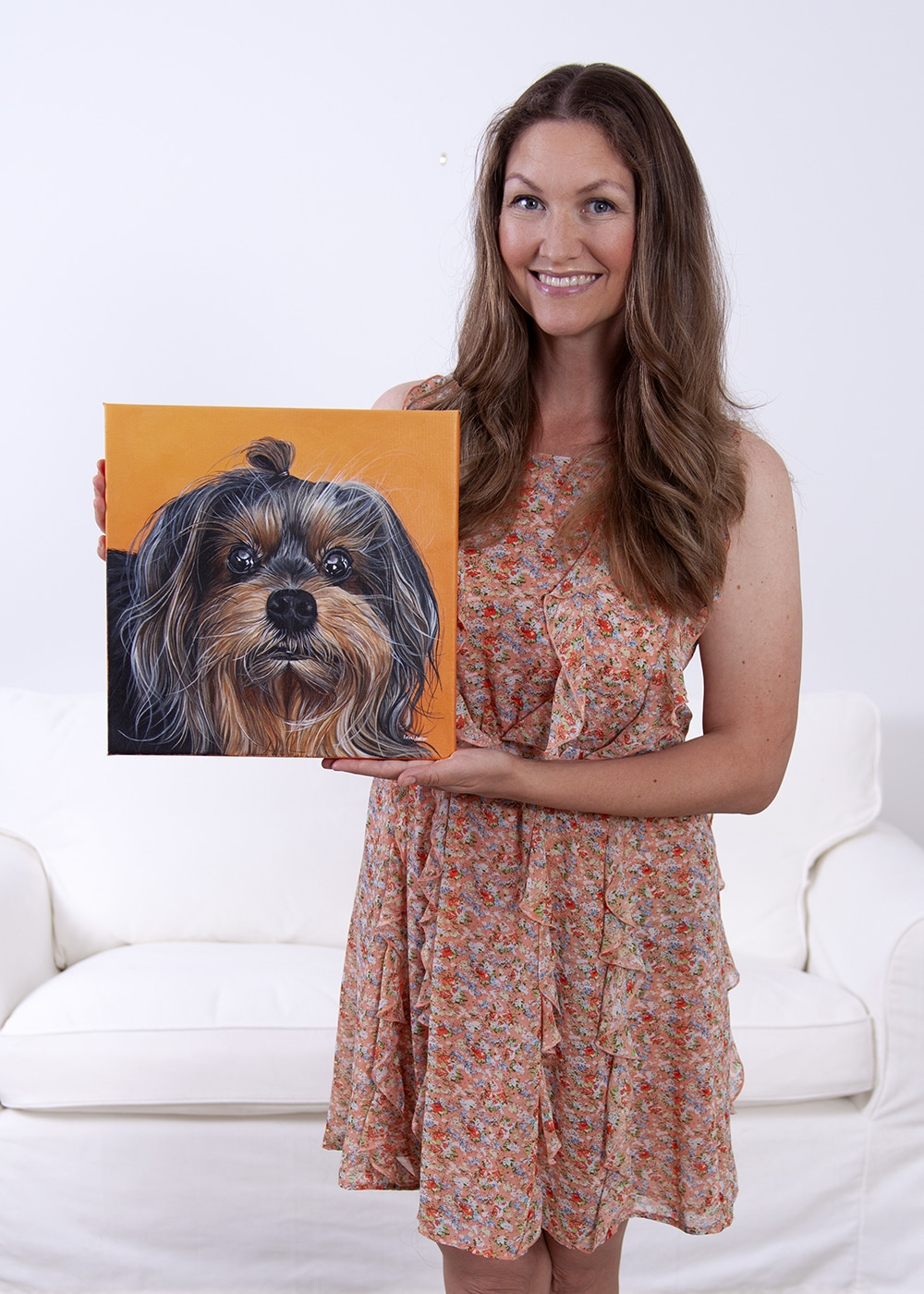 Fine arts painter Erica Eriksdotter holds a custom dog portrait of a yorkshire terrier